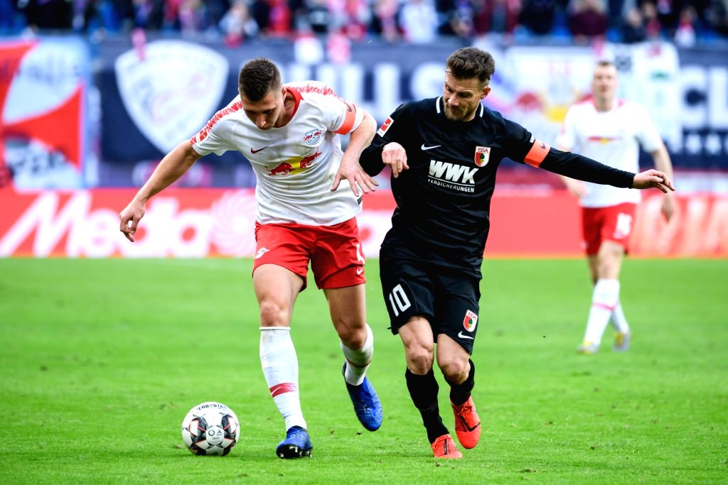 LEIPZIG, March 10, 2019 - Leipzig's Willi Orban (L) vies with Augsburg's Daniel Baier during a German Bundesliga match between RB Leipzig and FC Augsburg, in Leipzig, Germany, on March 9, 2019. The ...