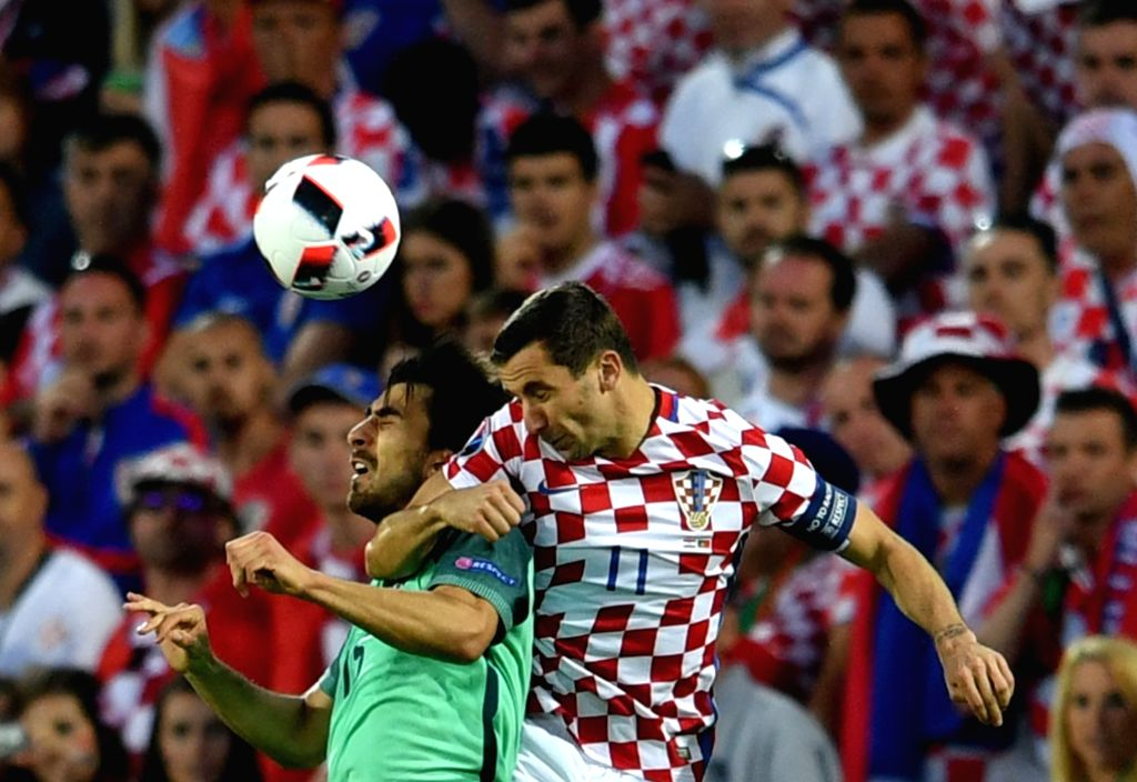 LENS, June 26, 2016 - Andre Gomes (L) of Portugal vies with Darijo Srna of Croatia during the Euro 2016 round of 16 soccer match between Portugal and Croatia in Lens, France, on June 25, 2016.