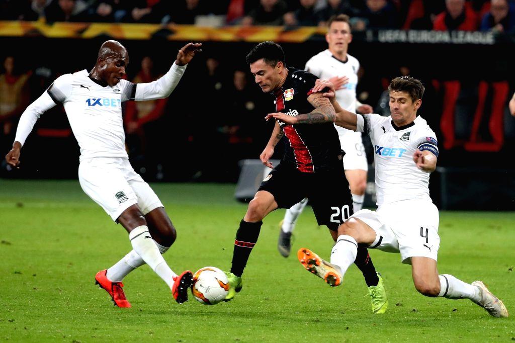 LEVERKUSEN, Feb. 22, 2019 - Charles Aranguiz (C) of Leverkusen vies with Charles Kabore (L) and Aleksandr Martynovich of Krasnodar during the UEFA Europa League round of 32 second leg soccer match ...