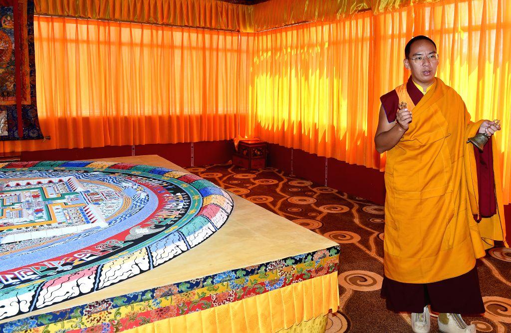 LHASA, July 26, 2016 - The 11th Panchen Lama Bainqen Erdini Qoigyijabu is seen near a mandala made of colored sand in Xigaze, southwest China's Tibet Autonomous Region, July 25, 2016. The first ...