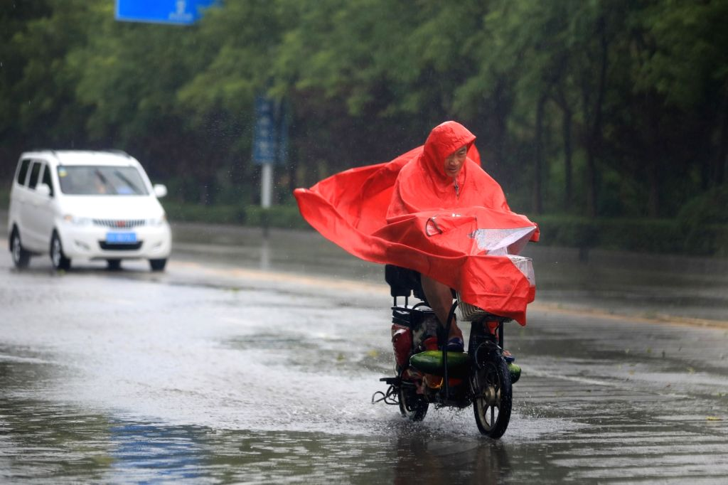 LIANYUNGANG, July 23, 2018 - A man rides in the rain on a street in Lianyungang City, east China's Jiangsu Province, July 23, 2018. Ampil, this year's 10th typhoon, brought heavy rain to Lianyungang ...