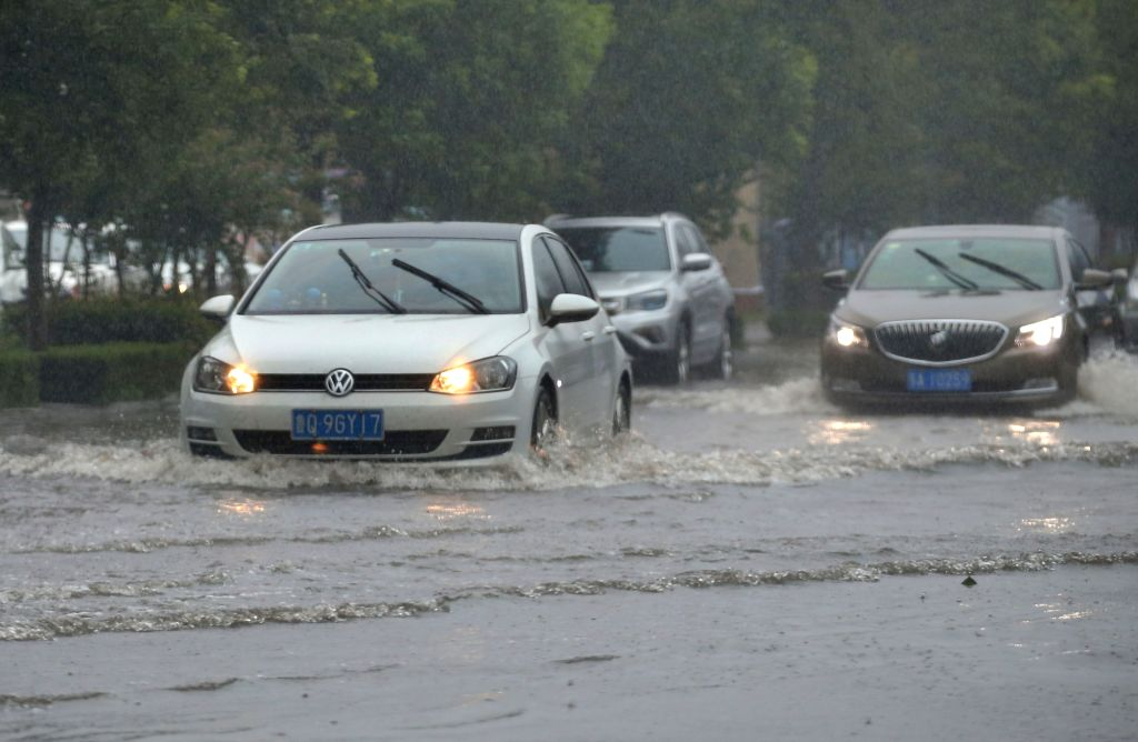 LIANYUNGANG, July 23, 2018 - Cars drive through a waterlogged street in Lianyungang City, east China's Jiangsu Province, July 23, 2018. Ampil, this year's 10th typhoon, brought heavy rain to ...
