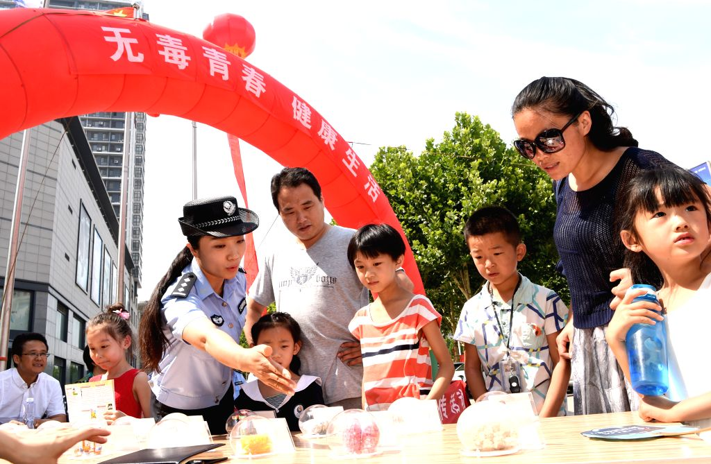 LIAOCHENG, June 26, 2016 - A policewoman introduces harm of drug to children in Liaocheng, east China's Shandong Province, June 26, 2016. A variety of educational activities were held across the ...