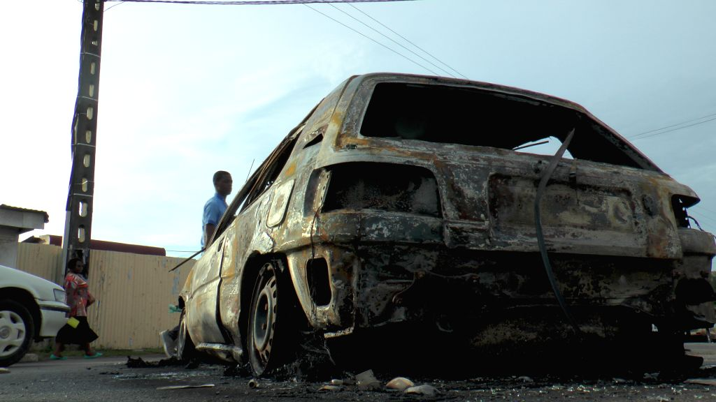Photo taken on April 13, 2015 shows a damaged car in Libreville, Gabon. Beninese Embassy in Gabon and three vehicles were razed down after violence broke out on ...