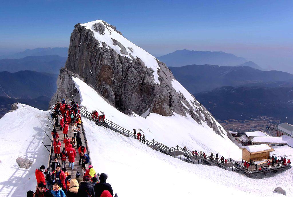 Tourists climb the Yulong jokul in Lijiang City, southwest China's Yunnan Province, Jan. 29, 2015.