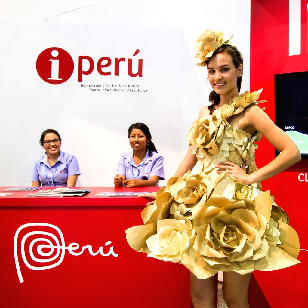 A staff member in a dress made of recycled paper stands in front of the reception of Peru Pavilion in the Pentagonito COP 20 conference center in Lima, capital of Peru, Dec. 3, 2014. (Xinhua/Xu