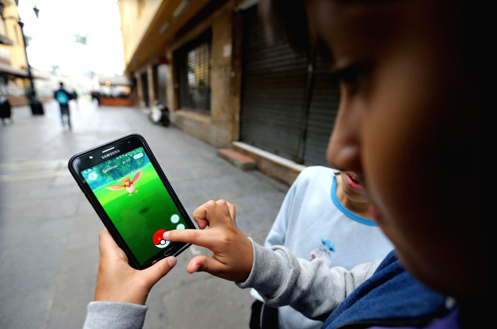 """LIMA, Aug. 8, 2016 (Xinhua) -- Children play """"Pokemon Go"""" on a smartphone at Plaza Mayor in Lima, capital of Peru, on Aug. 7, 2016. """"Pokemon Go"""" is a popular augmented reality game played on smartphones and tablets, in which players are required to e"""