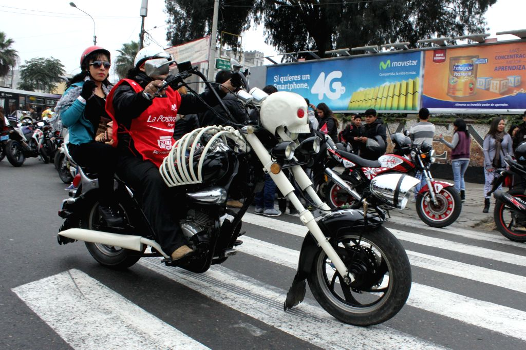"""A motorcyclist and a woman take part in the """"Patriotic Motorcycle Parade 2014"""" in Lima city, capital of Peru, on July 20, 2014. Motorcyclists took part in ..."""