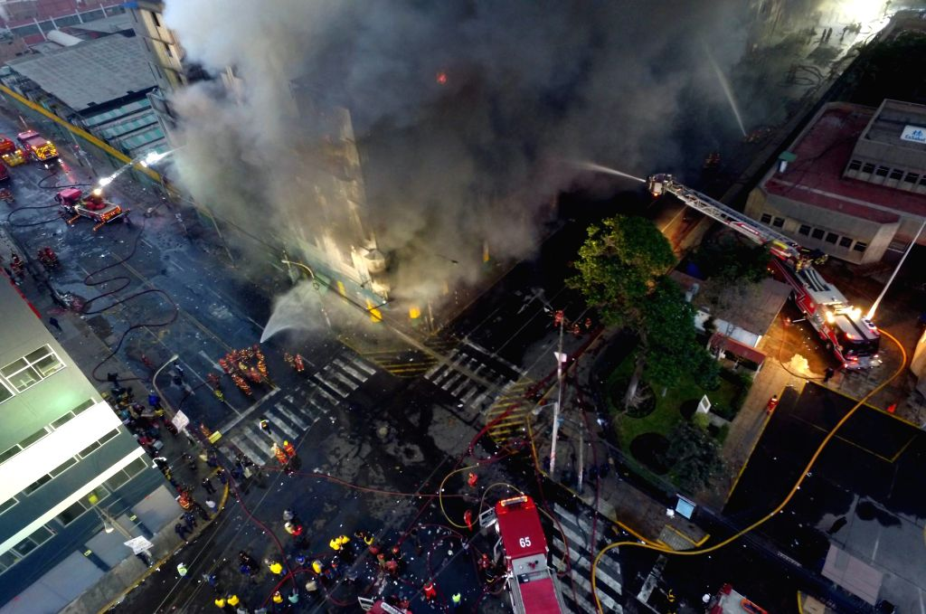 LIMA, June 24, 2017 - Firefighters try to extinguish the fire of a building near the Las Malvinas shopping area in Lima, Peru, June 23, 2017.