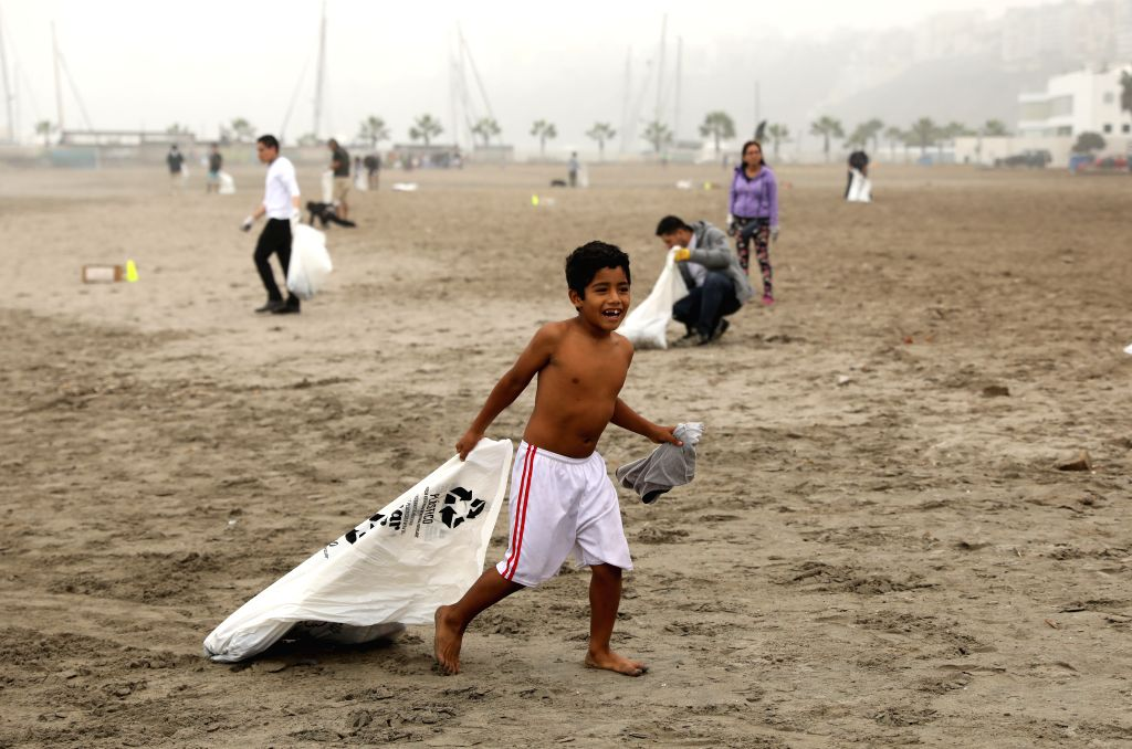 LIMA, June 9, 2019 - A boy cleans up the beach in Lima, Peru, June 8, 2019. People in Lima participated in a voluntary event to mark the World Oceans Day, a UN-designated day held annually on June 8, ...