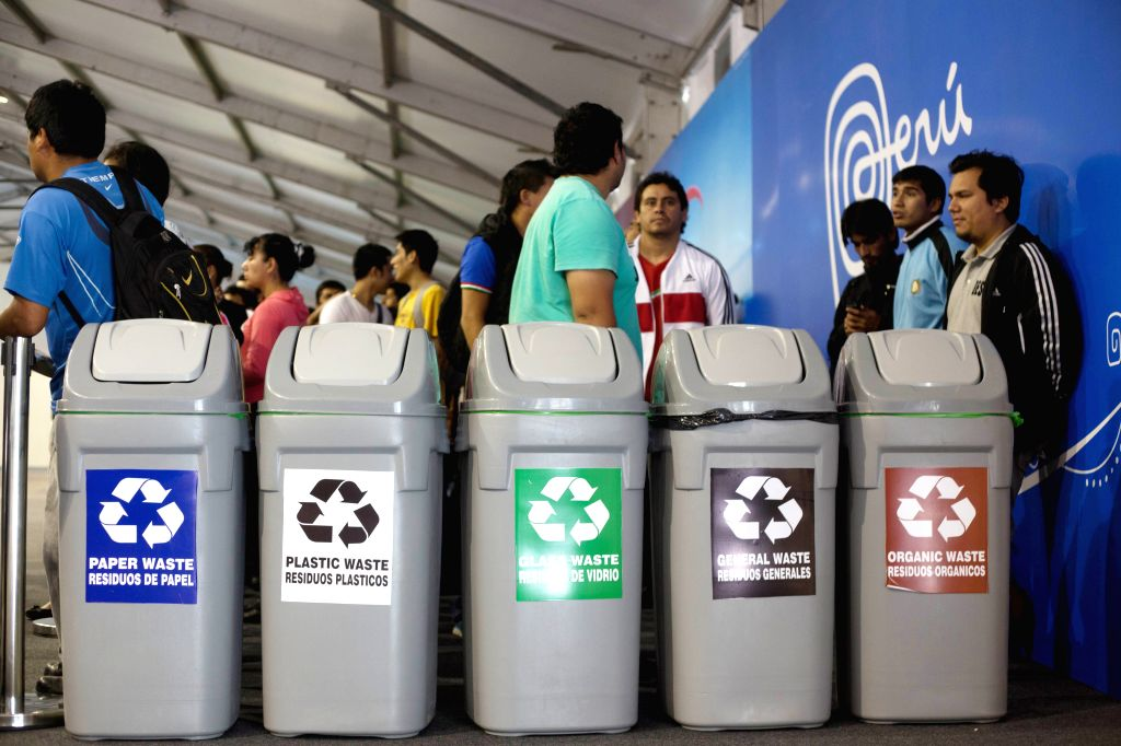 Lima (Peru): People stand beside dustbins outside the meeting hall of the UN COP 20/CMP 10 20th session of the Conference of the Parties and the 10th session of the Conference of the Parties, serving