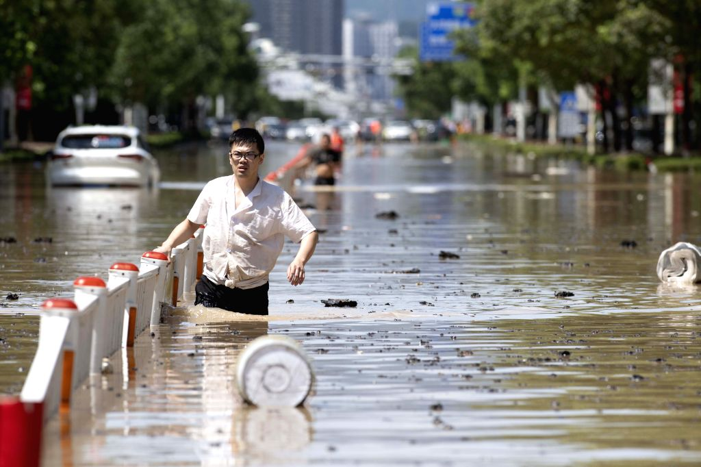 LINHAI, Aug. 11, 2019 - A man walks on waterlogged road in Linhai, east China's Zhejiang Province, Aug. 11, 2019. More than 21,000 service personnel and militia members have been engaged in rescue ...