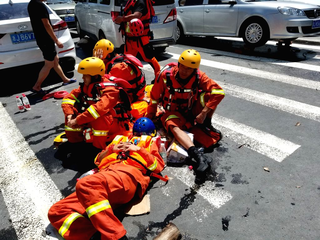 LINHAI, Aug. 11, 2019 - Rescue workers rest on road in Linhai, east China's Zhejiang Province, Aug. 11, 2019. More than 21,000 service personnel and militia members have been engaged in rescue and ...