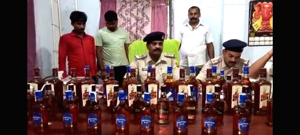 Liquor recovered from a police vehicle carrying 'logos', 2 arrested