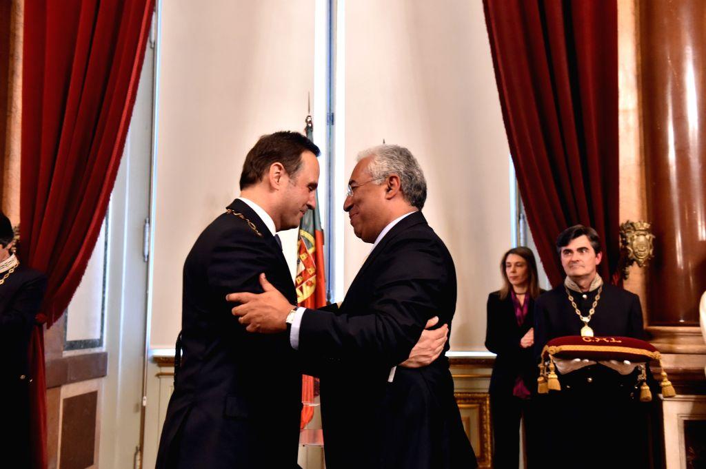 Lisbon's new mayor Fernando Medina(L) hugs former mayor Antonio Costa(R, front) during the swearing-in ceremony in Lisbon, Portugal, on April 6, 2015. Economist ...
