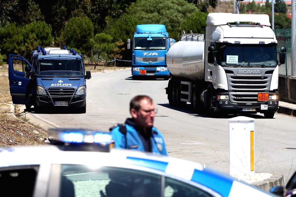 LISBON, Aug. 12, 2019 - A police officer escorts fuel-tankers leaving the Humberto Delgado Airport in Lisbon, Portugal, on Aug. 12, 2019. Portuguese fuel-tanker drivers' national strike began as ...