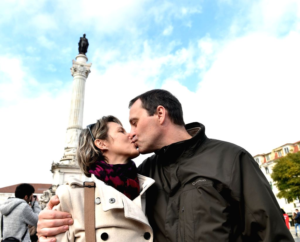A couple kiss during a charity event at the Rossio square in Lisbon, Portugal, Feb. 14, 2015. Hundreds of people celebrated the Valentine's Day by placing a padlock .