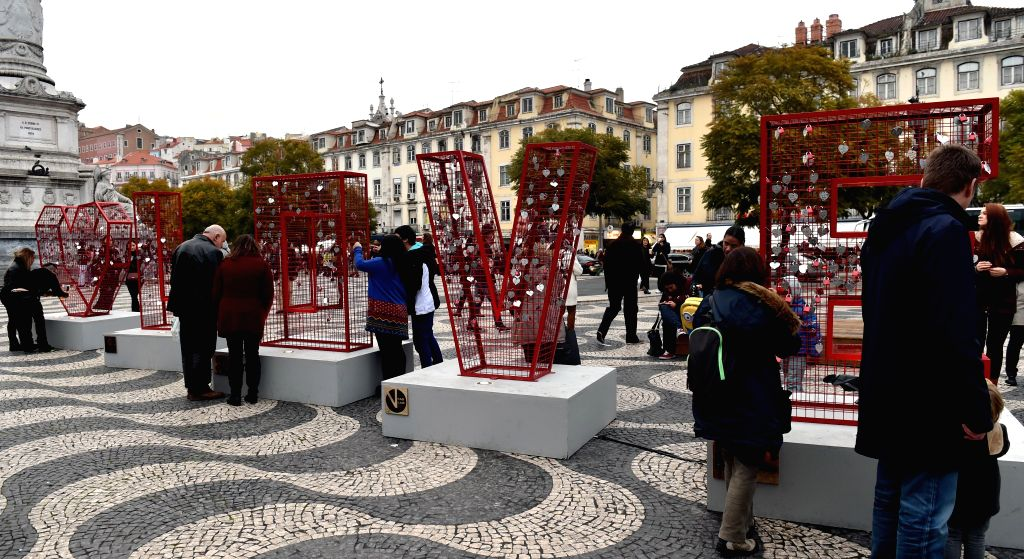 People attend a charity event beside a sculpture at the Rossio square in Lisbon, Portugal, Feb. 14, 2015. Hundreds of people celebrated the Valentine's Day by ...