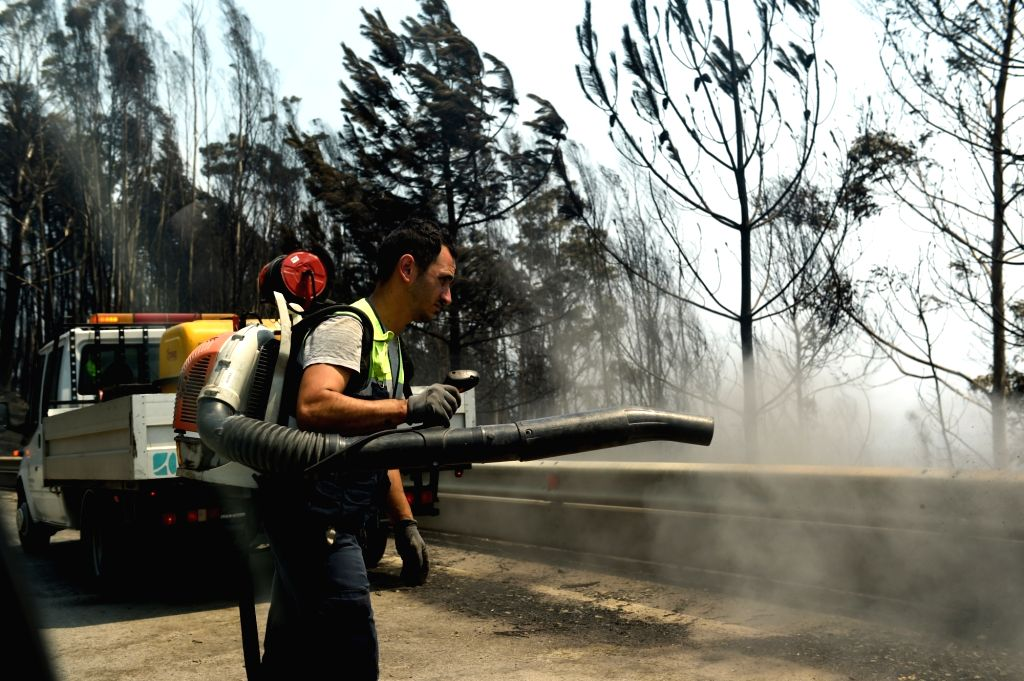 LISBON, June 18, 2017 - A staff worker cleans up the site of forest fire in the area of Pedrogao Grande, central Portugal on June 18, 2017. The number of people killed in the forest fire raging in ...