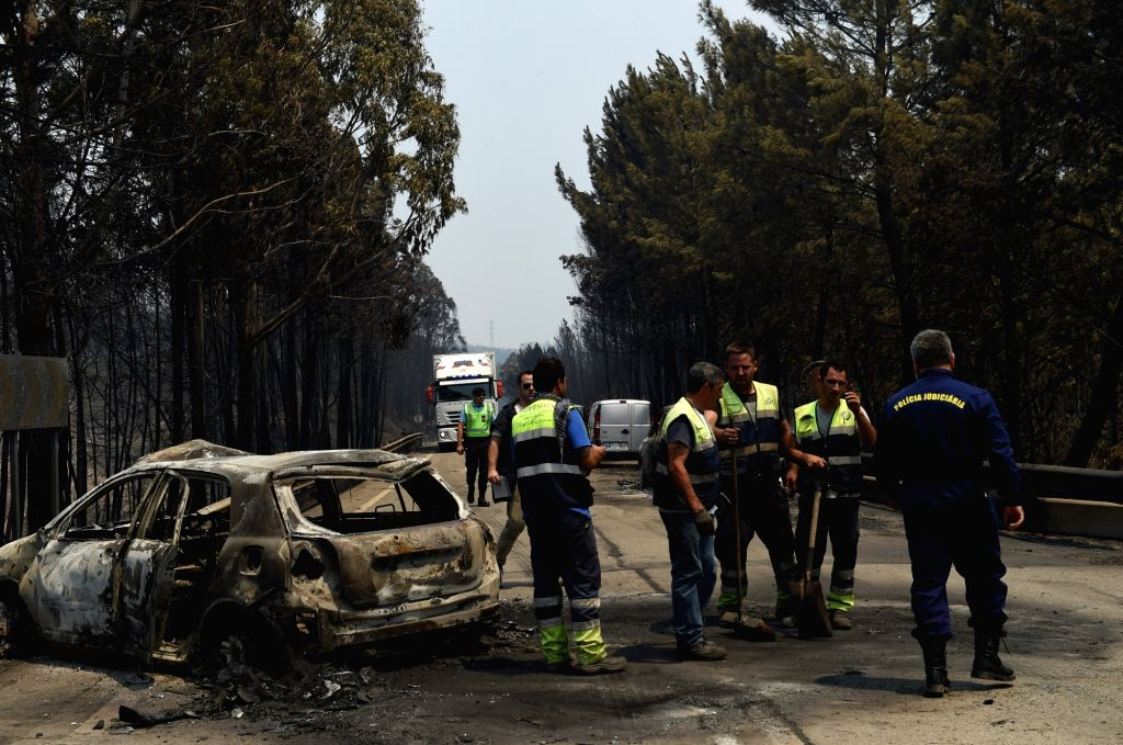 LISBON, June 18, 2017 - Staff workers clean up the site of forest fire in the area of Pedrogao Grande, central Portugal on June 18, 2017. The number of people killed in the forest fire raging in ...