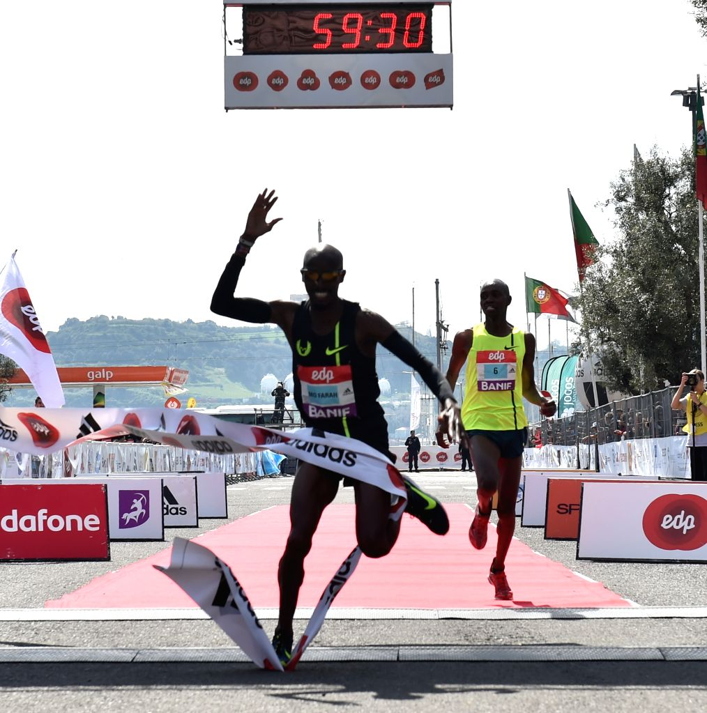 Mo Farah (L) of Britain falls after crossing the finish line of the 25th Lisbon Half Marathon race in Lisbon, Portugal on Mar. 22, 2015. Mo Farah took the first ...