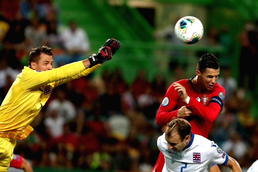 LISBON, Oct. 12, 2019 - Cristiano Ronaldo (R, top) of Portugal vies with Luxembourg's goalkeeper Anthony Moris (L) during the UEFA Euro 2020 qualifying round Group B match between Portugal and ...