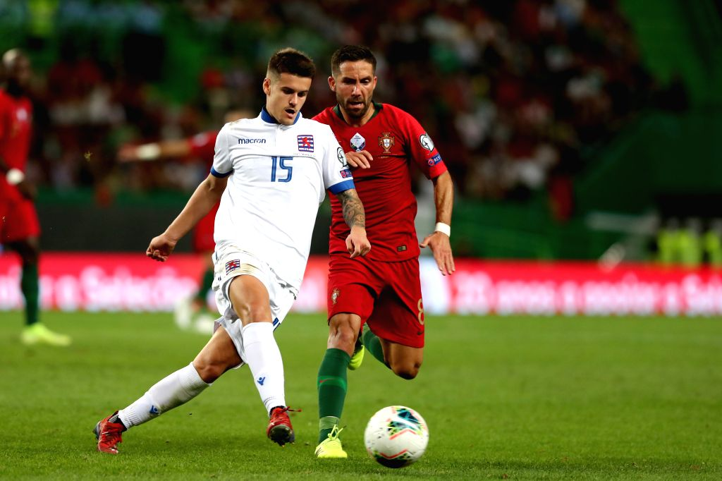 LISBON, Oct. 12, 2019 - Olivier Thill (L) of Luxembourg vies with Joao Moutinho of Portugal during the UEFA Euro 2020 qualifying round Group B match between Portugal and Luxembourg in Lisbon, ...