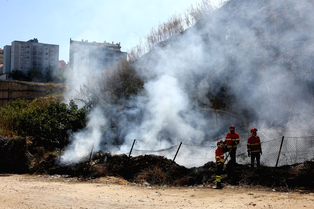 LISBON, Sept. 5, 2019 - Firefighters gather at the area where a bush fire broke out in Lisbon, Portugal, on Sept. 5, 2019. A bush fire broke out on Thursday in Lisbon, local media reported.