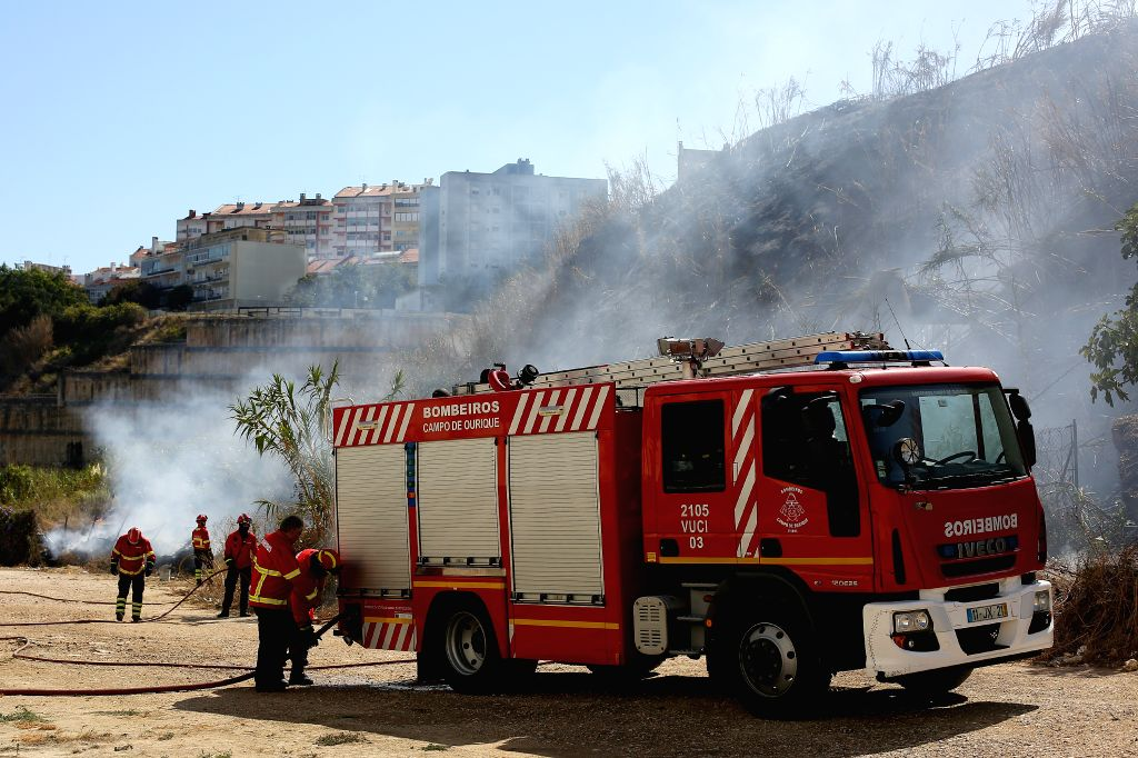 LISBON, Sept. 5, 2019 - Firefighters try to extinguish a bush fire in Lisbon, Portugal, on Sept. 5, 2019. A bush fire broke out on Thursday in Lisbon, local media reported.