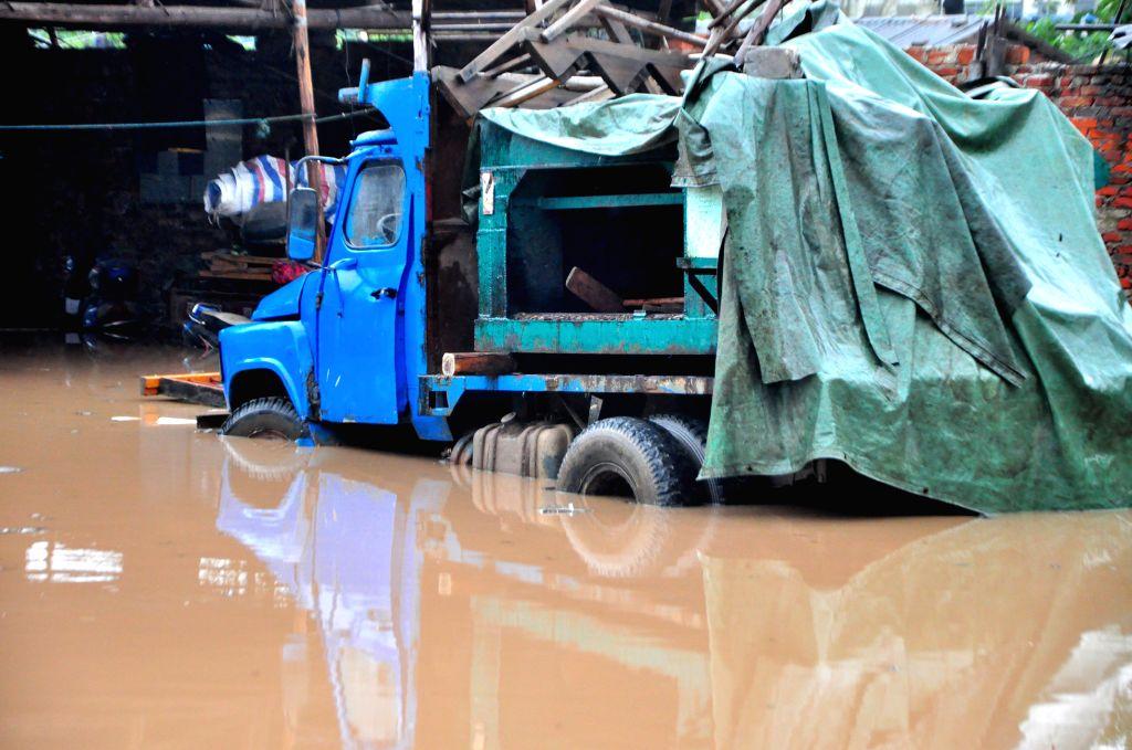 Water floods a truck at a wood processing plant after a rainstorm in Liuzhou City, south China's Guangxi Zhuang Autonomous Region, April 26, 2014. A rainstorm ...