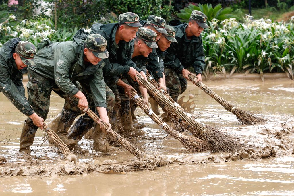 LIUZHOU, July 3, 2017 - Soldiers clear away mud after a flood at Riverside Park in Liucheng County of Liuzhou City, south China's Guangxi Zhuang Autonomous Region, July 3, 2017. Works of epidemic ...
