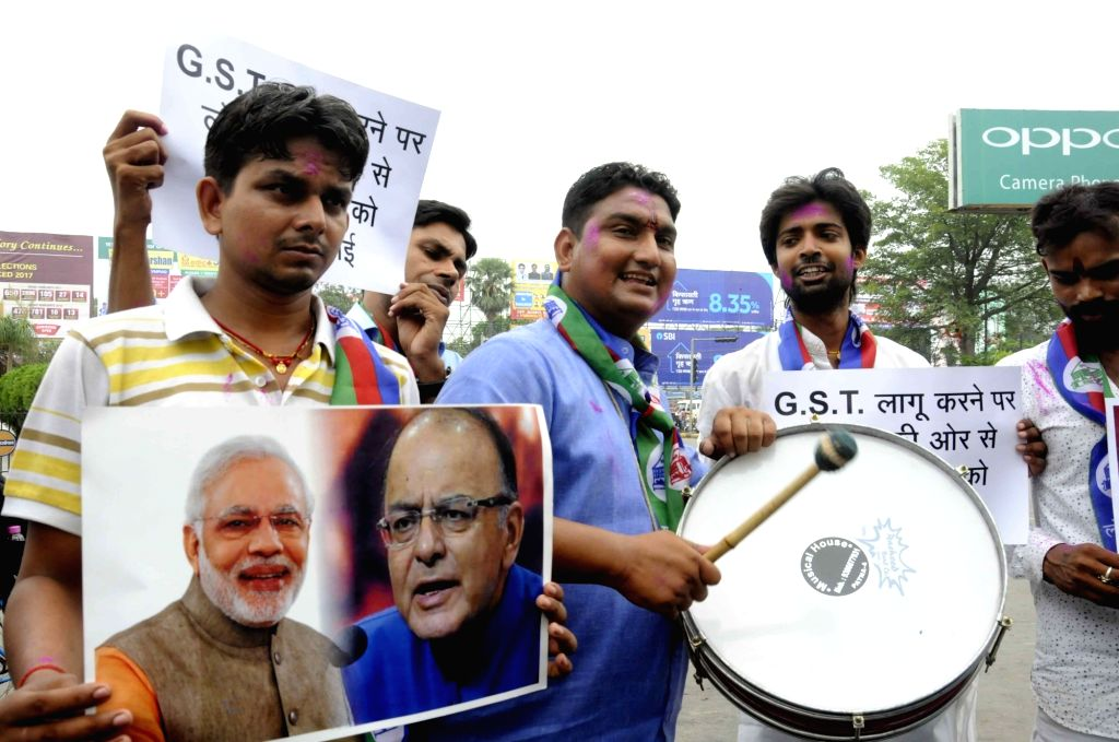LJP workers celebrate after launch of the Goods and Services Tax (GST) in Patna on Jul 1, 2017. At the stroke of the midnight hour, India launched its ambitious pan-India indirect tax regime, ...