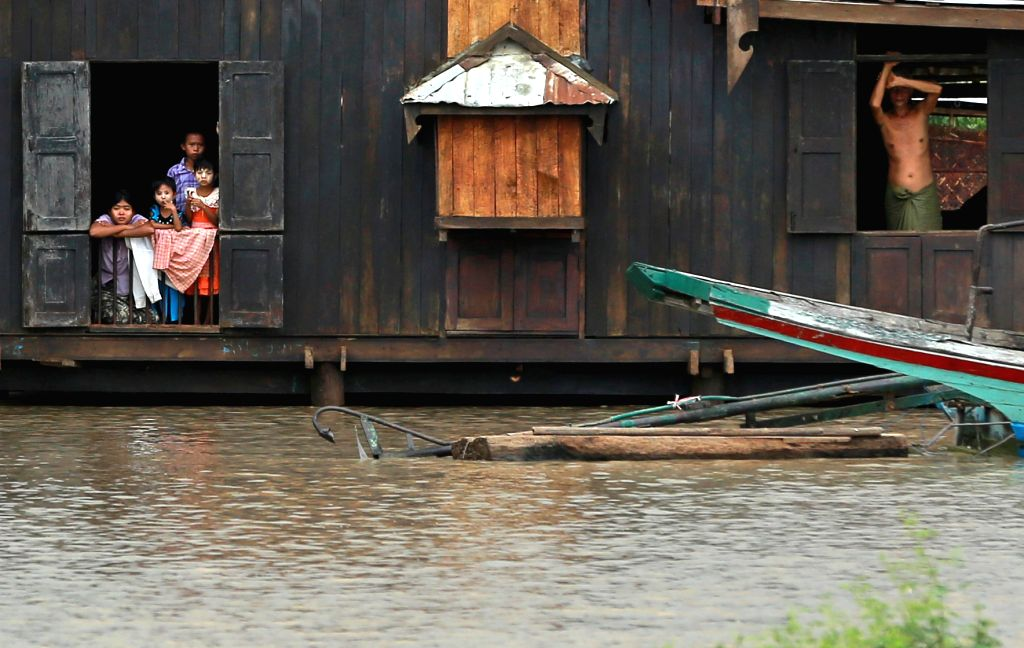 Local residents look out from their flooded-house at a Minbu district in Magway region, Myanmar, Aug 2, 2015. Heavy monsoon rains have left at least 47 people ...