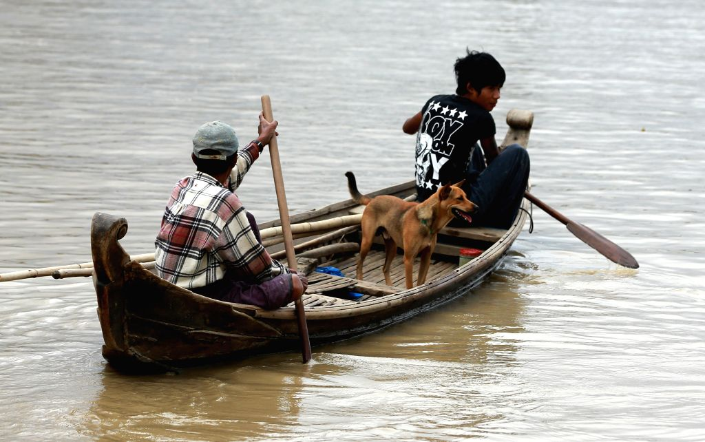 Local residents paddle their boat in a flooded area at a Minbu district in Magway region, Myanmar, Aug 2, 2015. Heavy monsoon rains have left at least 47 ...