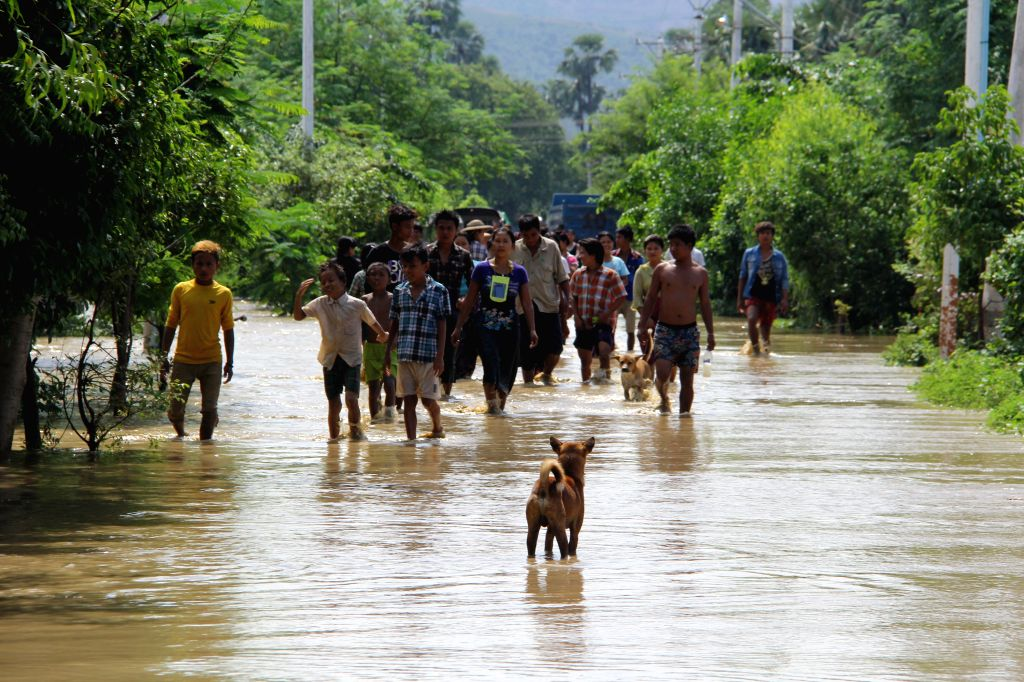 Local residents wade through a flooded area in Salingyi Township of Sagaing Region, Myanamr, Aug. 2, 2015. Death toll from severe flooding across Myanmar rose to 69, ...