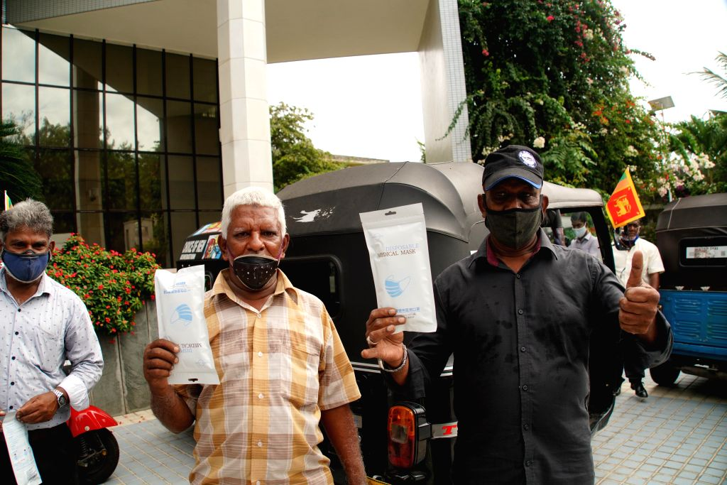 Local three-wheel drivers pose with face masks during a donation ceremony in Colombo, Sri Lanka, July 29, 2020. The Chinese Embassy to Sri Lanka on Wednesday ...
