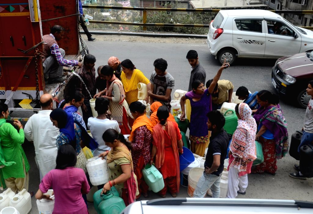 Locals gather around a water tanker to collect water amid water crisis that has affected many parts of the country during summers, in Shimla on May 31, 2018. Shimla is facing a water crisis ...