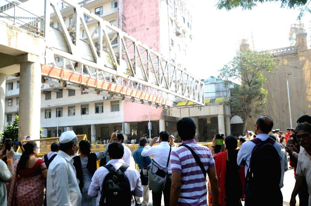 Locals gather at the site where a portion of a pedestrian bridge crashed near the Chhatrapati Shivaji Maharaj Terminus , in Mumbai on March 15, 2019.
