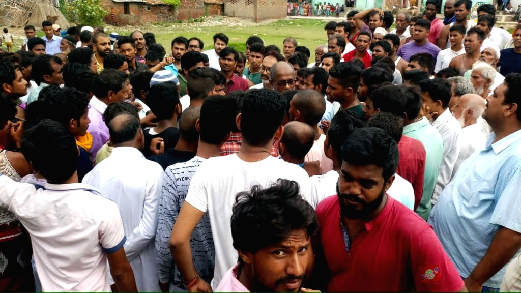 Locals gather at the site where three men were allegedly thrashed to death and one critically injured by villagers over suspicion of cattle theft in Bihar's Saran district on July 19, 2019. ...