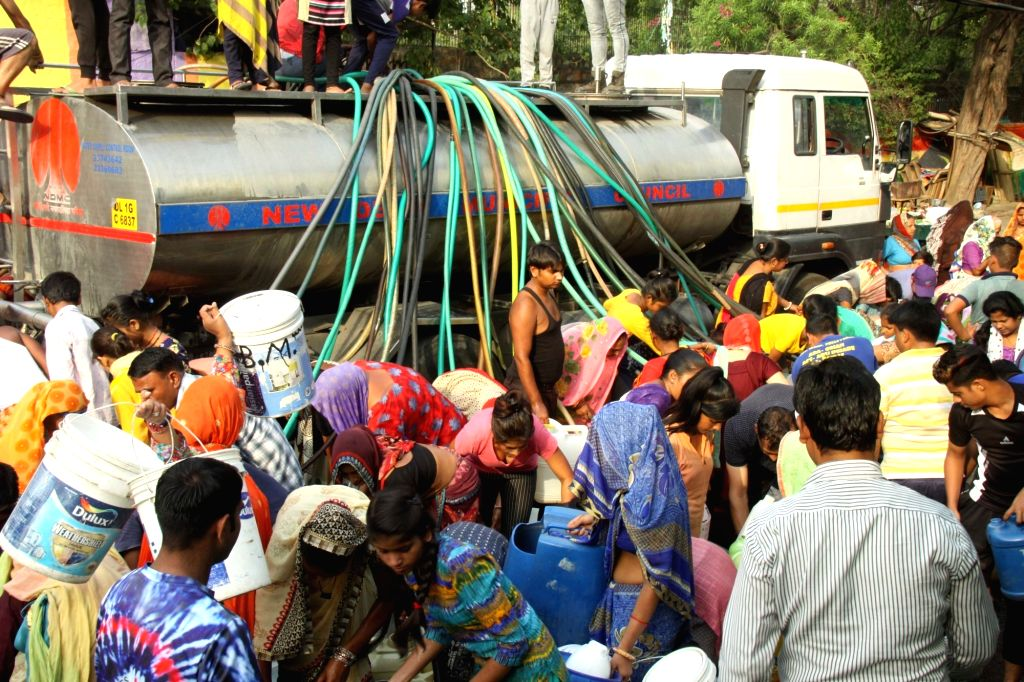 Locals gather to collect water from a water tanker amid water shortage in Chanakyapuri, New Delhi on June 6, 2019.