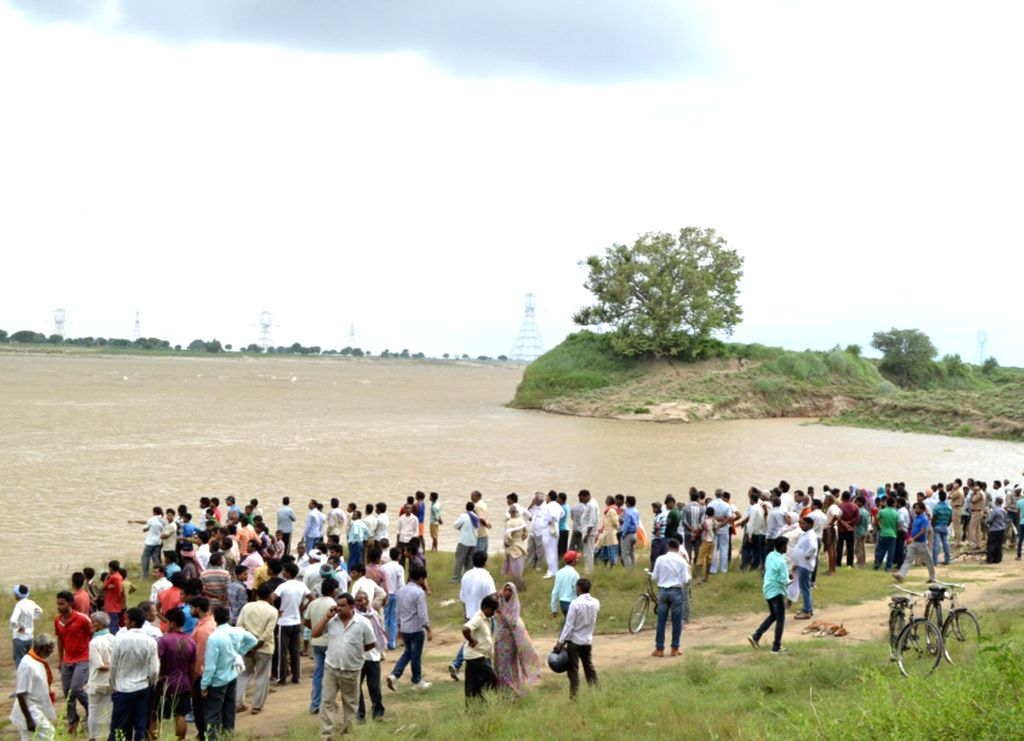 Locals watch rescue work as as a boat capsizes in the Ganga river in Mirzapur district on Aug. 5, 2014.