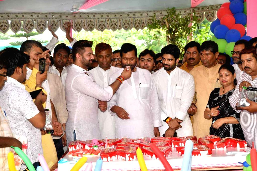 Lok Janshakti Party (LJP) leader Chirag Paswan fetches cake to his father and party chief  Ram Vilas Paswan during the latter's birthday celebrations, in Patna on July 5, 2018.