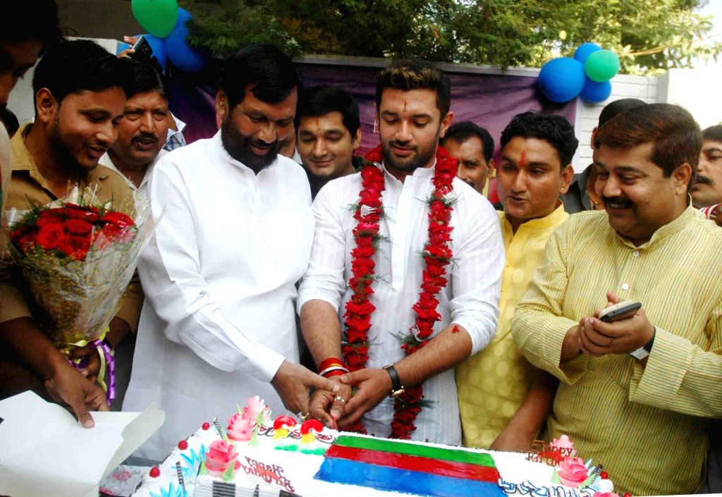 Lok Janshakti Party`s Jamui MP Chirag Paswan with his father and Union Minister for Consumer Affairs, Food and Public Distribution Ramvilas Paswan cuts a cake during a programme organised by ...