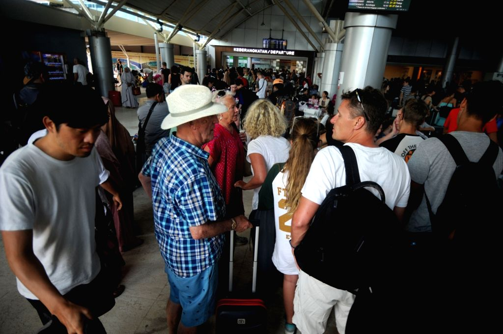 LOMBOK, Aug. 6, 2018 - Tourists wait to check in at Praya International airport on Lombok Island, Indonesia, Aug. 6, 2018. The death toll rose to 91 and the number of injured people was up to 209 ...