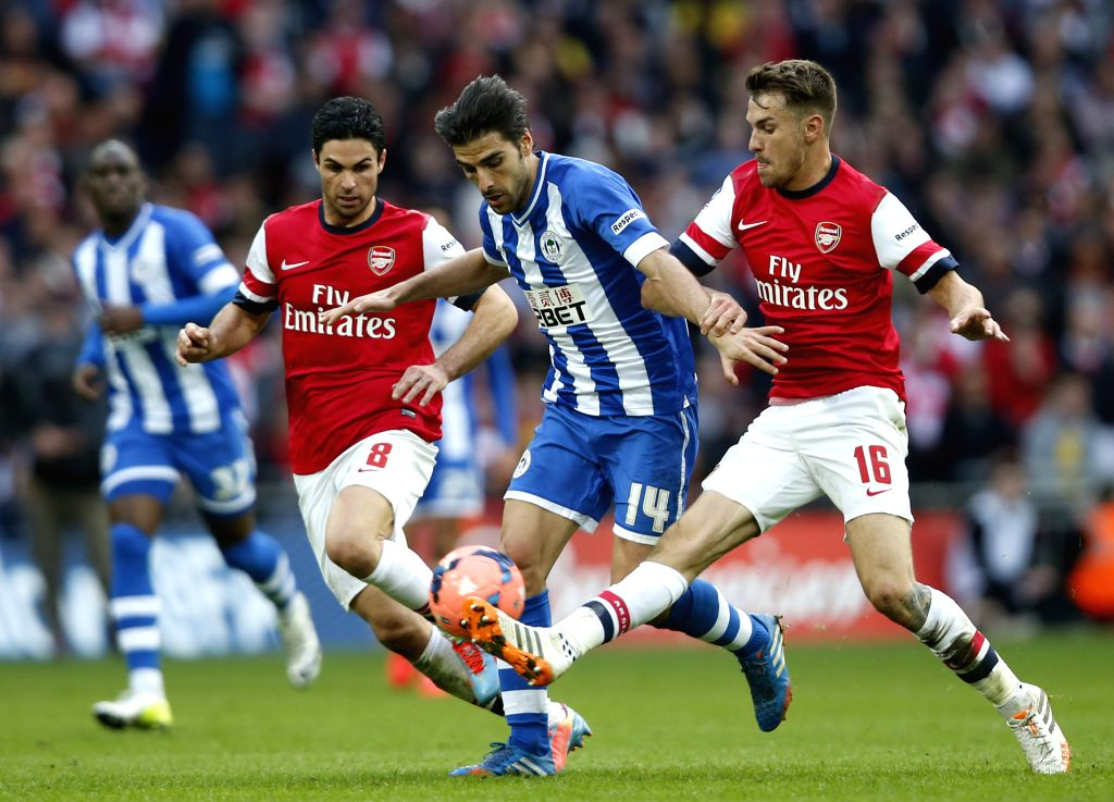 Aaron Ramsey (1st, R) of Arsenal vies with  Jordi Gomez (2nd, R) of Wigan Athletic during FA Cup semifinal match between Arsenal and Wigan Athletic at Wembley ...