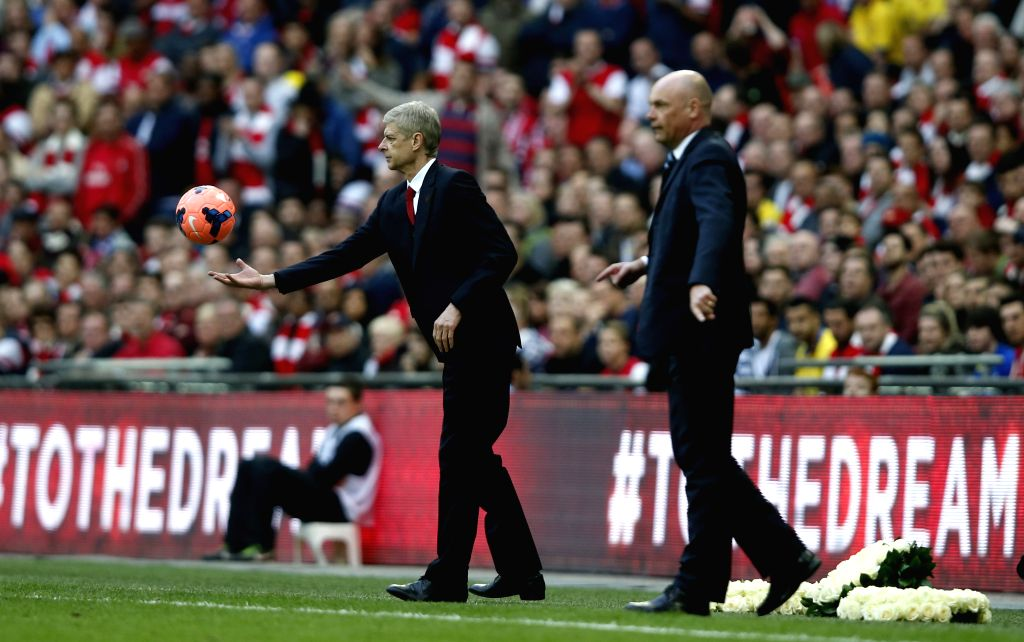 Arsene Wenger (L), manager of Arsenal and Uwe Rosler, manager of Wigan Athletic, look on during FA Cup semifinal match between Arsenal and Wigan Athletic at Wembley