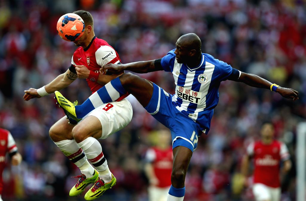 Emmerson Boyce (R) of Wigan Athletic vies with Lukas Podolski of Arsenal during FA Cup semifinal match between Arsenal and Wigan Athletic at Wembley Stadium in ...