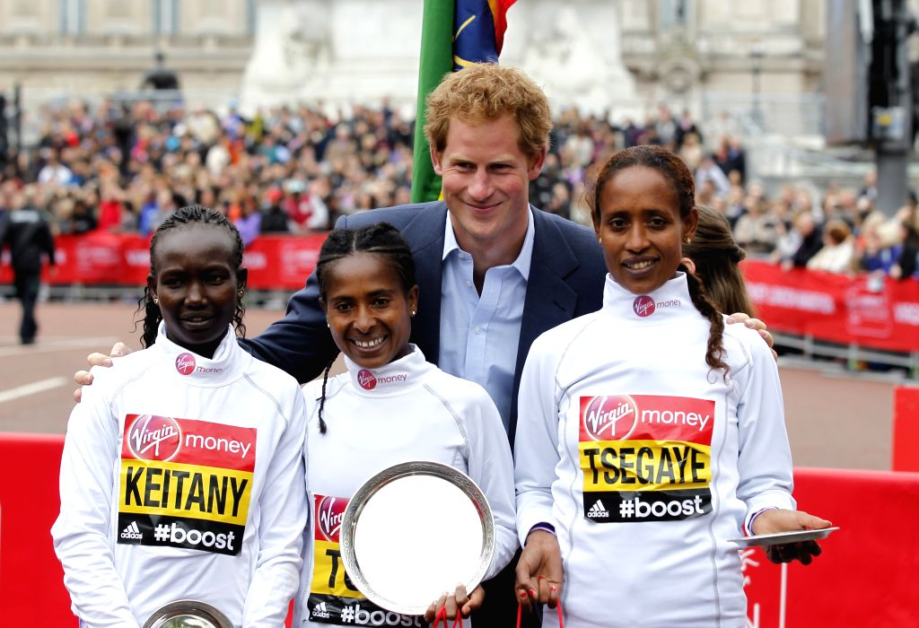 Britain's Prince Harry poses for a picture with winners of the Women's race Mary Keitany of Kenya(L) who came second, Tigist Tufa of Ethiopia(C) who came first and ...