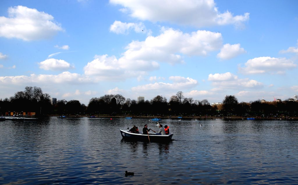 People row their boat on a lake in central London, Britain on April 7, 2015.