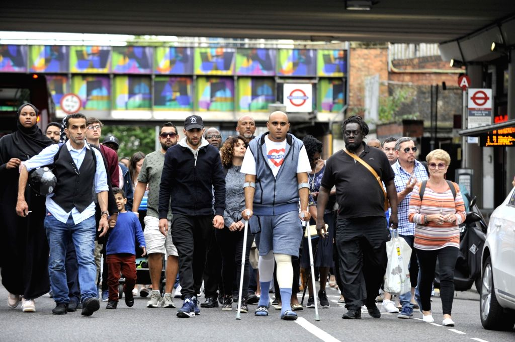 LONDON, Aug. 14, 2017 - People take part in a silent and peaceful march to pay respects to the victims of the Grenfell Tower fire in London, Britain, on Aug. 14, 2017. At least 80 people were ...